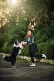 Młoda dziewczyna i jej psi Border collie bawić się outdoors obrazy royalty free