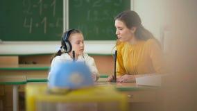 Młoda dziewczyna i nauczyciel używa w sala lekcyjnej hełmofony i mikrofon zbiory wideo