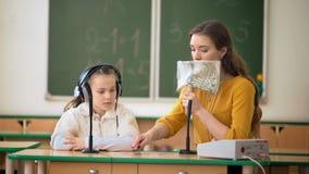 Młoda dziewczyna i nauczyciel używa w sala lekcyjnej hełmofony i mikrofon zdjęcie wideo