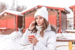 Młoda dziewczyna i piękny dzwonimy telefonem, trzyma filiżankę z gorącą kawą lub herbatą w ona ręki Uśmiechy w ciepłym obraz royalty free