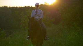 Młoda dziewczyna jeździec jedzie brown konia z białą baseball nakrętką zdjęcia stock
