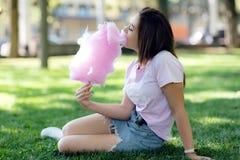 Młoda dziewczyna je bawełnianego cukierek w parku zdjęcie stock