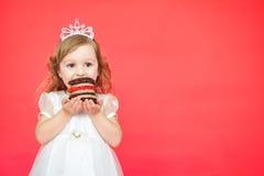 Młoda dziewczyna je mini urodzinowego tort nad czerwonym tłem Obrazy Royalty Free
