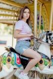 Młoda dziewczyna jedzie na carousel koniach z szkłami zdjęcia stock