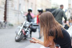 Młoda dziewczyna jest przyglądająca w smartphone który trzyma Kobieta siedzi na ławce w centrum antyczny miasto przeciw moto obrazy royalty free
