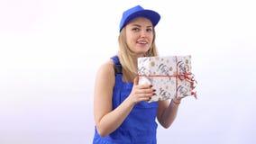 Młoda dziewczyna jest ubranym błękitnych kombinezony trząść Bożenarodzeniową teraźniejszość w rękach zbiory wideo