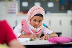 Młoda dziewczyna jest ubranym hijab studiowanie obrazy stock