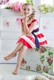 Młoda dziewczyna jest ubranym suknię z rocznik walizką Zdjęcia Stock