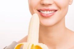 Młoda dziewczyna jest wokoło jeść banana Obraz Royalty Free