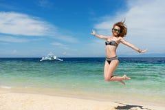 Młoda dziewczyna juming na plaży z białym niebieskim niebem i piaskiem Obrazy Royalty Free
