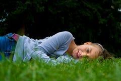 Młoda dziewczyna kłaść na boku w trawy ono uśmiecha się Zdjęcie Stock