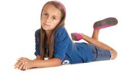 Młoda dziewczyna kłaść na ziemi podpierającej up na jej łokciach Zdjęcie Royalty Free