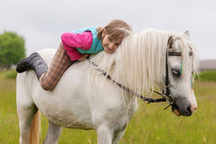 Młoda dziewczyna kłama na białego konia plecy Fotografia Royalty Free
