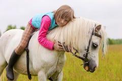 Młoda dziewczyna kłama na białego konia plecy Fotografia Stock