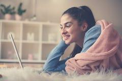Młoda dziewczyna kłama na podłoga i używa laptop w domu fotografia royalty free