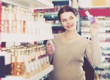 Młoda dziewczyna klient szuka dla silnego pachnidła obraz stock