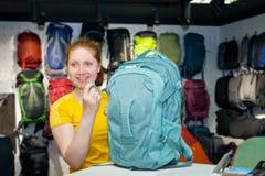 Młoda dziewczyna konsultant w specjalność sklepie dla turystyki podnosi plecaka obrazy stock