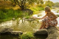 Młoda dziewczyna kropi wodę blisko jeziora Zdjęcie Royalty Free