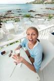 Młoda dziewczyna ma kawową przerwę w widok na ocean kawiarni zdjęcia stock