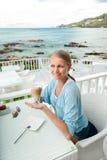 Młoda dziewczyna ma kawową przerwę w widok na ocean kawiarni zdjęcie royalty free