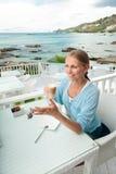 Młoda dziewczyna ma kawową przerwę w widok na ocean kawiarni Fotografia Stock
