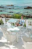Młoda dziewczyna ma kawową przerwę w widok na ocean kawiarni obrazy royalty free