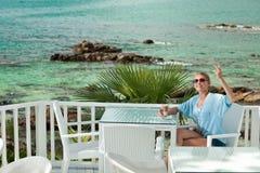 Młoda dziewczyna ma kawową przerwę w widok na ocean kawiarni zdjęcie stock