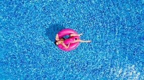 Młoda dziewczyna ma zabawę, śmia się zabawę i ma w basenie na nadmuchiwanym różowym flamingu w kostiumu kąpielowym w lecie od abo Fotografia Stock