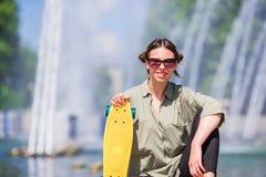 Młoda dziewczyna ma zabawę z deskorolka w parku Stylu życia portret młoda pozytywna kobieta ma zabawę i cieszy się ciepłego Zdjęcie Royalty Free