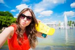 Młoda dziewczyna ma zabawę z deskorolka w parku Stylu życia portret młoda pozytywna kobieta ma zabawę i cieszy się ciepłego Zdjęcia Royalty Free