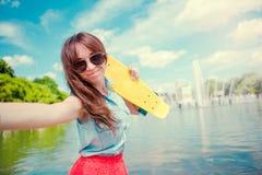 Młoda dziewczyna ma zabawę z deskorolka w parku Stylu życia portret młoda pozytywna kobieta ma zabawę i cieszy się ciepłego Zdjęcia Stock