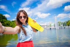 Młoda dziewczyna ma zabawę z deskorolka w parku Stylu życia portret młoda pozytywna kobieta ma zabawę i cieszy się ciepłego Obraz Royalty Free