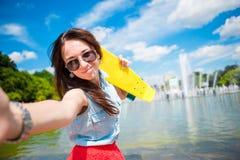 Młoda dziewczyna ma zabawę z deskorolka w parku Stylu życia portret młoda pozytywna kobieta ma zabawę i cieszy się ciepłego Obrazy Stock