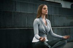 Młoda dziewczyna medytuje na schodkach Zdjęcie Royalty Free