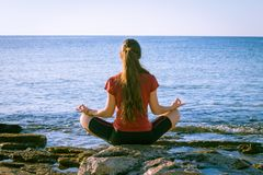 Młoda dziewczyna medytuje na wybrzeżu w joga pozie Obrazy Royalty Free