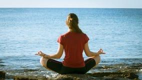 Młoda dziewczyna medytuje na wybrzeżu w joga pozie zbiory