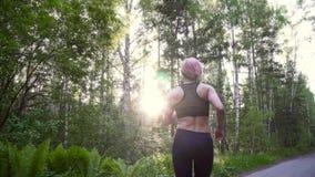 Młoda dziewczyna na bieg szkoleniu w lasowej atlecie w sportswear na szkoleniu swobodny ruch zbiory wideo