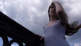 Młoda dziewczyna na bridżowym niebieskiego nieba tle z podmuchowym włosy w wiatrowy przyglądający up zbiory