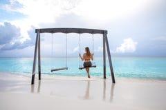 Młoda dziewczyna na huśtawce nad wodą Fotografia Stock