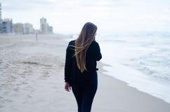 Młoda dziewczyna na jego z powrotem, chodzący na plaży na chmurnym dniu zdjęcia royalty free