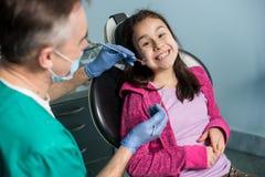 Młoda dziewczyna na pierwszy stomatologicznej wizycie Starszy męski dentysta robi pierwszy badania kontrolne dla pacjenta przy st Fotografia Royalty Free