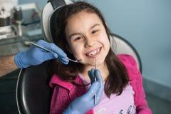 Młoda dziewczyna na pierwszy stomatologicznej wizycie Starszy męski dentysta robi pierwszy badania kontrolne dla pacjenta przy st Zdjęcie Royalty Free