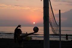 Młoda dziewczyna na plaży, trzyma balowy w rękach Siatkówek sieci na plaży obraz royalty free