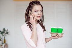 Młoda dziewczyna na popielatym tle z dreadlocks fryzurą, trzyma właściciela z dwa takeaway filiżankami zdjęcia stock