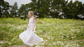 Młoda dziewczyna nastolatek z włosianym warkocza doskakiwaniem na zielonej łące przy latem Romantyczna nastolatek dziewczyna wiru zdjęcie wideo