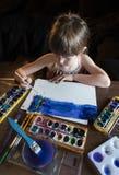 Młoda dziewczyna obraz z akwarelami maluje z błękitem Zdjęcie Stock