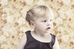 Młoda dziewczyna ono uśmiecha się przeciw kwiecistemu tłu Zdjęcia Stock