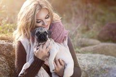 Młoda dziewczyna ono uśmiecha się z mopsa psem Obraz Royalty Free
