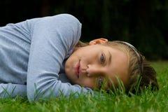 Młoda dziewczyna ono uśmiecha się z otwartym usta kłaść na boku w trawie Fotografia Royalty Free