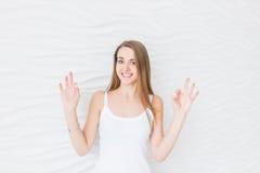 Młoda dziewczyna ono uśmiecha się z szczęśliwą twarzą w białym singlet pokazuje ok ręka znaka Zdjęcie Stock